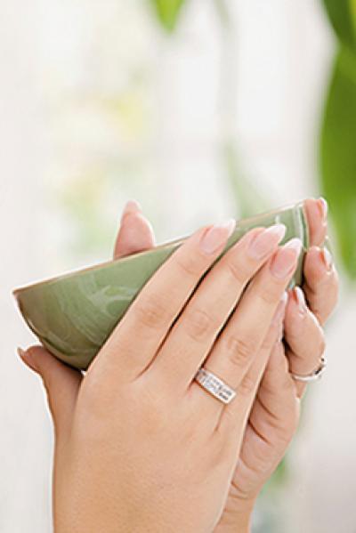 Hände halten eine grüne Teeschale